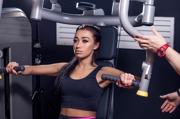 Concetto di sport, fitness, lavoro di squadra e persone. giovane donna che flette i muscoli sulla macchina della palestra e personal trainer con appunti