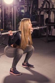 Sport, fitness, formazione e concetto di felicità - donna sportiva con bilanciere in palestra.