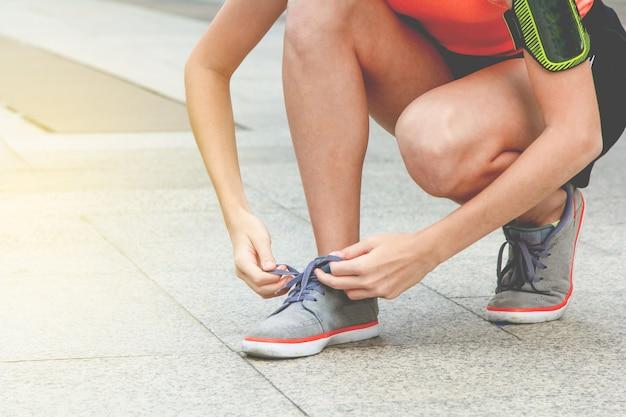 Le atlete sportive sono lacci delle scarpe per prepararsi al jogging