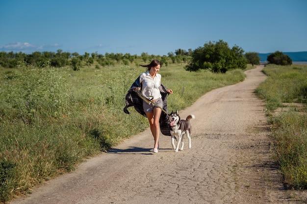 La ragazza di sport sta correndo con un cane il husky siberiano sulla strada