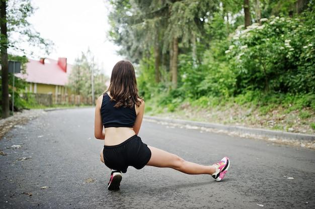 Metta in mostra la ragazza agli abiti sportivi che si esercitano in un parco verde e che si preparano alla natura.