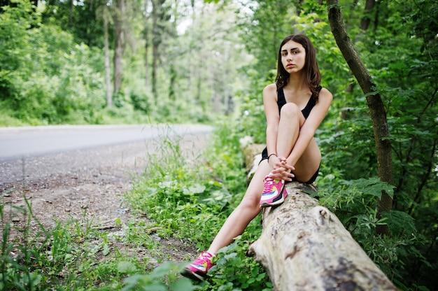 Metta in mostra la ragazza agli abiti sportivi che hanno il resto in un parco verde dopo l'allenamento alla natura.