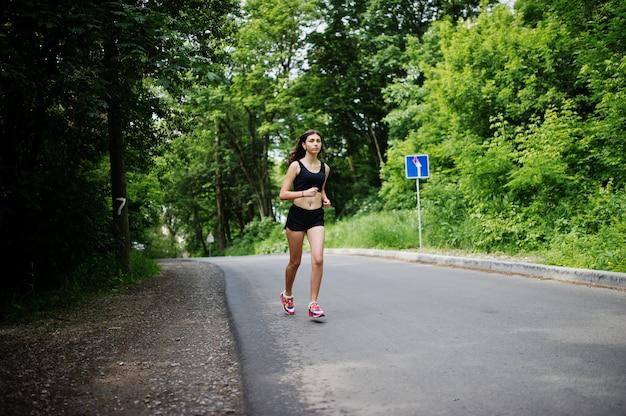 Metta in mostra la ragazza agli abiti sportivi che corrono in un parco verde e che si preparano alla natura.