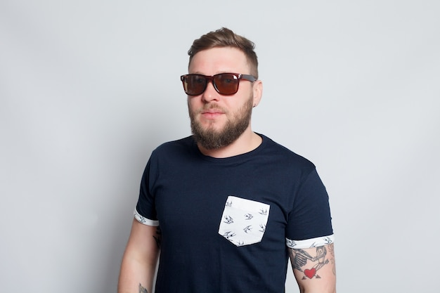 Sport, salute, persone, 4k e concetto di stile di vita - moda ritratto di giovane uomo barbuto. ragazzo hipster sorridente. bell'uomo con il cappello. ragazzo barbuto brutale con tatuaggio