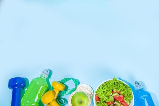 Sport stile di vita sano, concetto di dieta. dimagrante sfondo fitness perdita di peso con metro a nastro, manubri colorati, insalata, pane croccante ai cereali, bottiglia d'acqua sportiva su sfondo blu copia spazio
