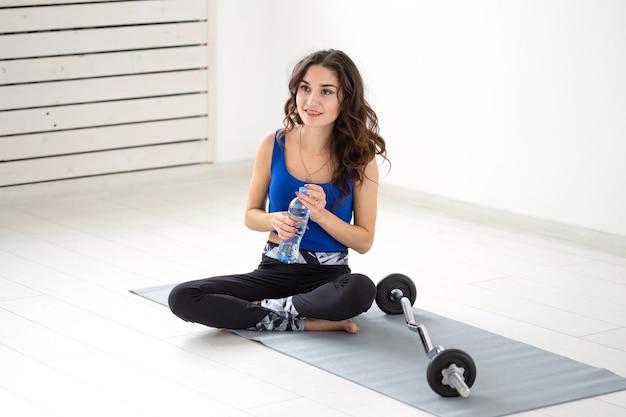 Sport, stile di vita sano, concetto di persone - acqua potabile della giovane donna dopo lo sport.
