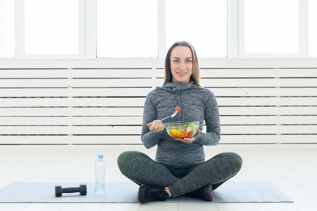 Sport, sano, concetto di persone - ragazza con insalata e manubri dopo l'allenamento fitness