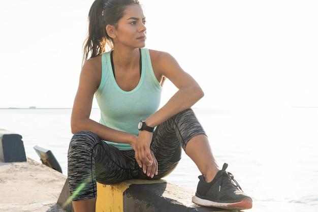 Concetto di sport e stile di vita - donna che riposa dopo aver fatto sport all'aperto. donna fitness prendendo una pausa dopo aver eseguito l'allenamento.