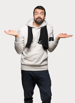 Uomo di sport che ha dubbi mentre alzando le mani e le spalle sopra fondo grigio isolato