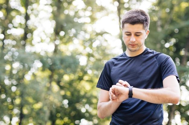 Uomo di sport che osserva orologio intelligente