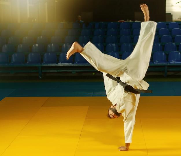 L'uomo sportivo in kimono bianco pratica la capoeira nel palazzetto dello sport