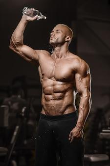 Metta in mostra l'acqua potabile dell'uomo muscolare di forma fisica dopo gli esercizi del muscolo dell'abs della palestra di concetto e di forma fisica dell'incrocio di allenamento nel concetto nudo di forma fisica del torso della palestra
