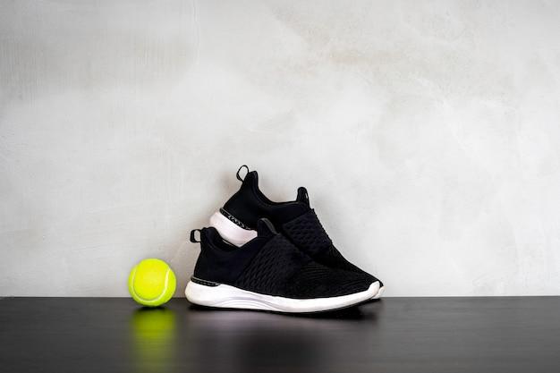 Scarpe sportive e palla da tennis