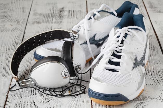 Scarpe sportive con le cuffie sulla parete di legno