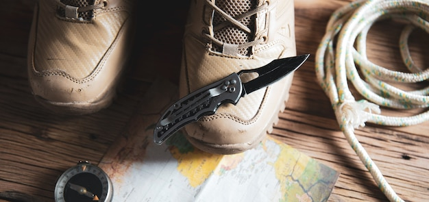 Scarpe sportive con coltello e bussola sulla mappa