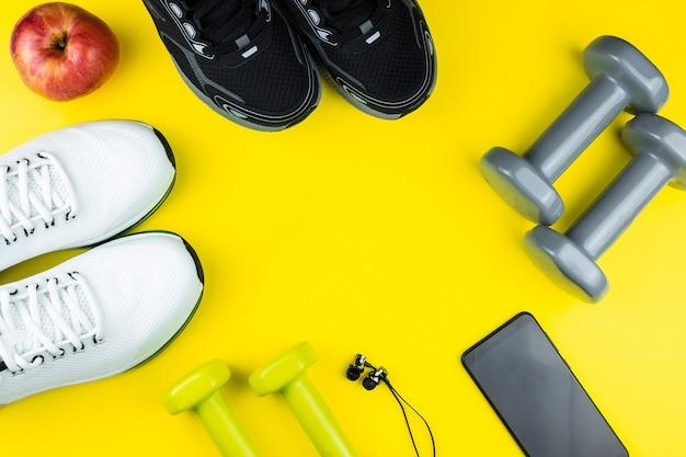 Scarpe sportive con telefono, cuffie e manubri