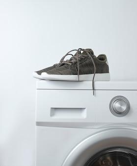 Metta in mostra le scarpe da tennis sulla lavatrice contro una superficie bianca