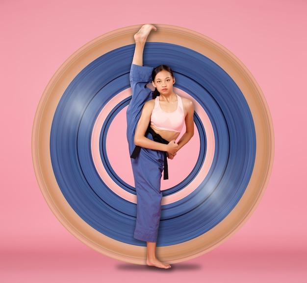 Sport l'allungamento della ragazza dell'adolescente solleva la gamba flessibile, fa pose alla moda. il bambino di 12-15 anni di atleta asiatico giovanile indossa pantaloni di stoffa rosa pastello su sfondo rosa a tutta lunghezza