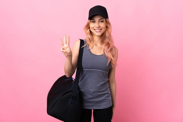 Ragazza adolescente sport con borsa sportiva sopra isolato felice e contando tre con le dita