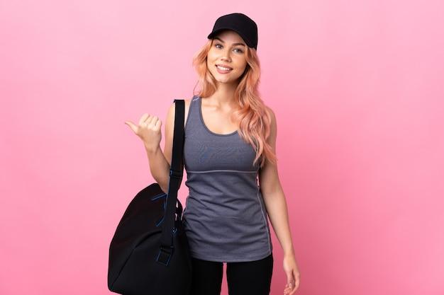 Ragazza dell'adolescente di sport con la borsa sportiva sopra isolato che punta al lato per presentare un prodotto