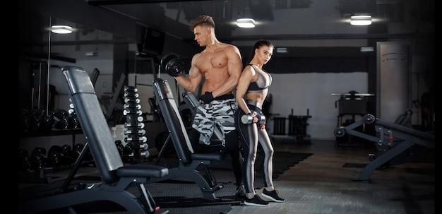Sport, allenamento, fitness, stile di vita e concetto di persone - giovane donna con personal trainer che flette la schiena e i muscoli addominali sulla panchina in palestra. foto di alta qualità