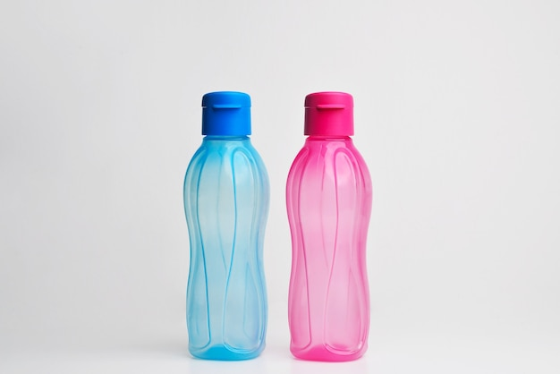 Bottiglia di sport watter acqua colorata bottiglie di plastica colorate contenitore di bottiglia di acqua liquida trasparente in sfondo bianco isolato