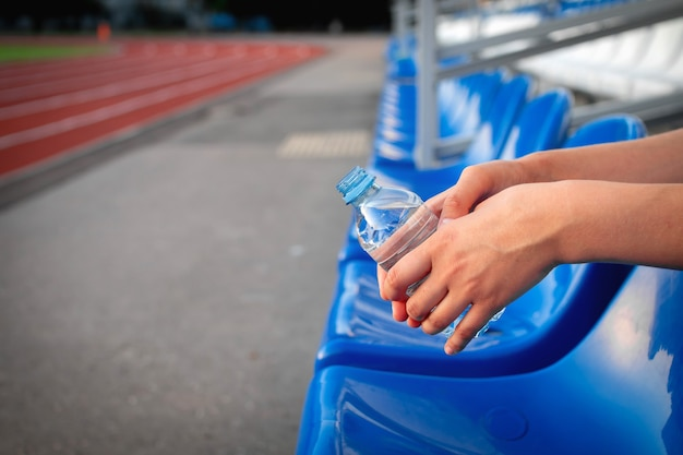 Sport e benessere. riposa dopo l'allenamento, bevi acqua per l'assistenza sanitaria e gli sport all'aria aperta al mattino in estate donna millenaria che tiene la bottiglia allo stadio fuori, primo piano, copia spazio