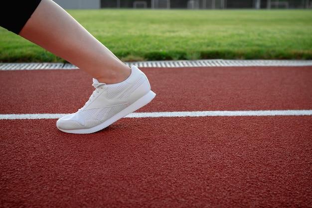 Sport e benessere. sportiva che pratica jogging nello stadio esterno. primo piano di una gamba femminile in scarpe da ginnastica bianche. scarpe sportive per la corsa. copia spazio