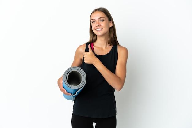 Donna sportiva che va alle lezioni di yoga mentre tiene in mano un tappetino su sfondo bianco isolato dando un gesto di pollice in su