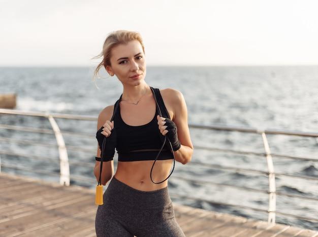 Kickboxer della donna di sport con le mani fasciate in bende e la posa della corda per saltare