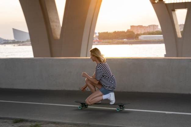 Donna sportiva che fa trucchi su skateboard da longboard per rilassarsi o hobby attivo al tramonto