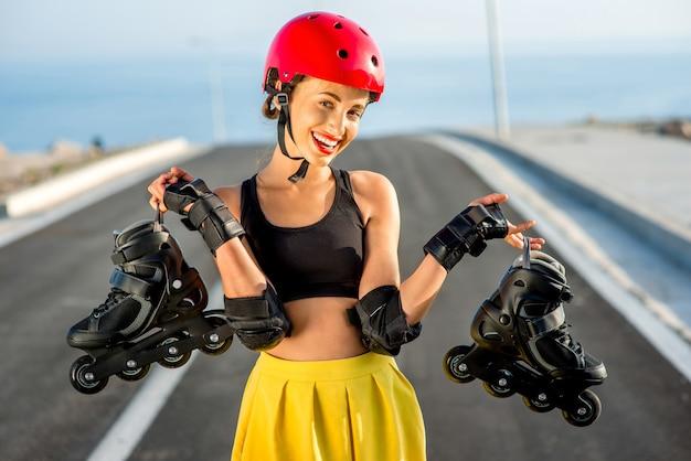 Donna di sport in casco rosso che tiene i rulli neri