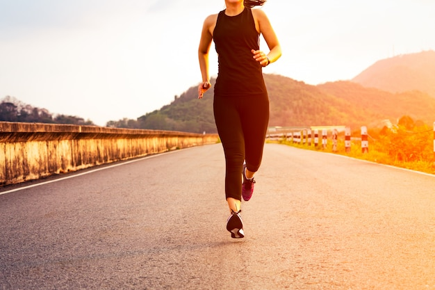Donna sportiva in esecuzione su una strada. addestramento della donna di forma fisica al tramonto