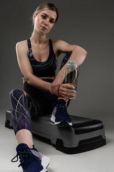 La donna di sport si siede con una bottiglia d'acqua dopo l'allenamento e rilassarsi