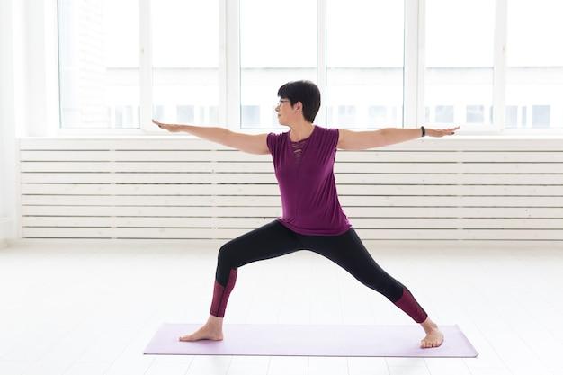 Sport, yoga, concetto di persone - donna di mezza età sportiva che pratica yoga al chiuso