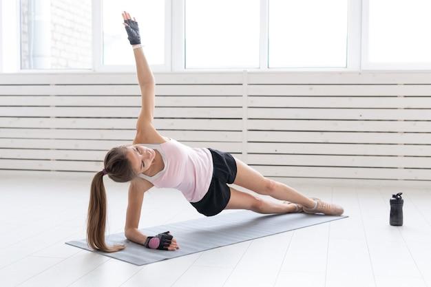 Concetto di sport, yoga e persone - la giovane donna sta facendo fitness. sta premendo sul pavimento in palestra.