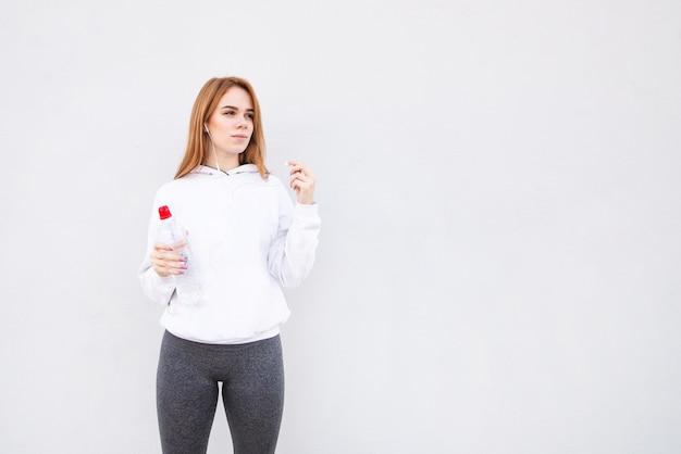 Sfoggia uno sfondo bianco con una bottiglia d'acqua in mano, guarda lateralmente e ascolta la musica