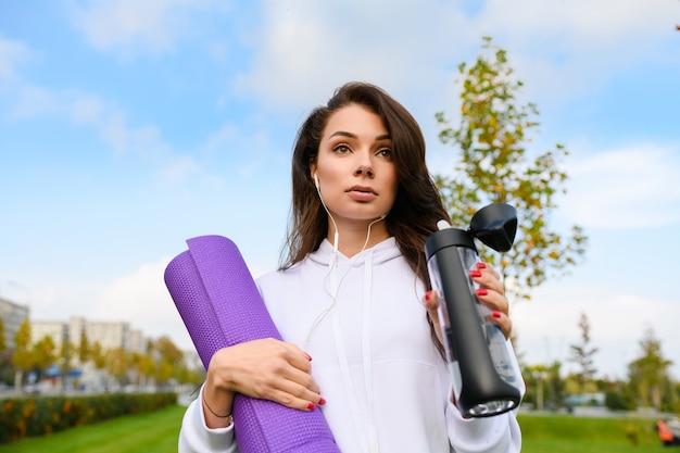 Donna bruna sportiva sullo sfondo del parco cittadino verde con tappetino viola, indossare le cuffie, bere acqua dopo l'allenamento, fitness, yoga all'aperto