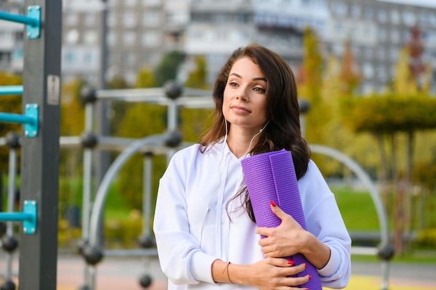 Donna bruna sportiva in posa con tappetino viola per esercizi, allenamento, fitness, yoga al parco giochi nel parco cittadino