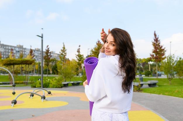 Donna bruna sportiva in felpa con cappuccio bianca tenere tappetino viola al parco giochi del parco cittadino, allenamento, fitness, stretching all'aperto