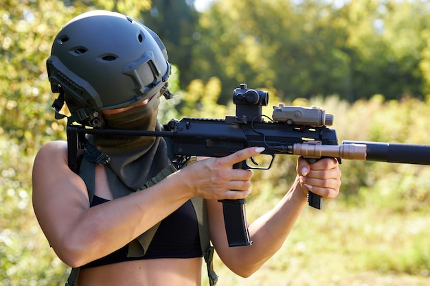 Soldato della donna caucasica sportiva che spara con la mitragliatrice del fucile nella foresta, giovane femmina sottile sta caccia
