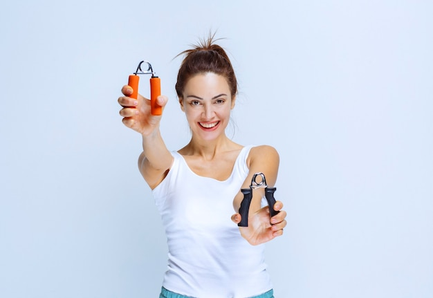 Ragazza sportiva che tiene impugnature di colore nero e arancione.