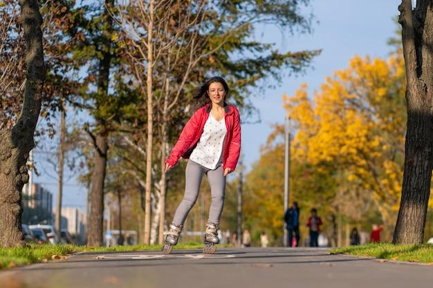 Una ragazza sportiva è rollerblade in un parco in autunno