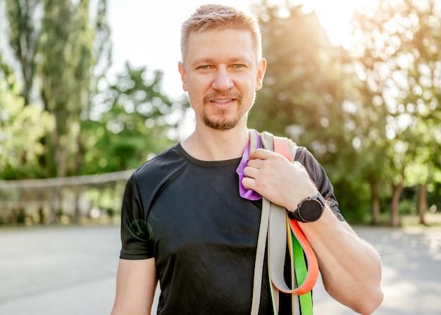 Ragazzo sportivo che tiene in mano un set di elastici colorati e sorride guardando la telecamera allo stadio all'aperto. atleta di sesso maschile durante l'allenamento con attrezzatura sportiva aggiuntiva