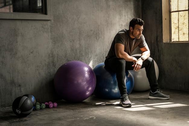Uomo sportivo che fa una pausa su una palla fitness