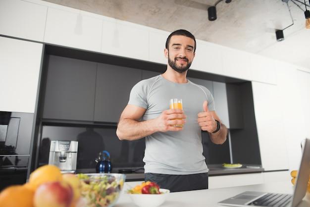 Un uomo sportivo è in posa in cucina.