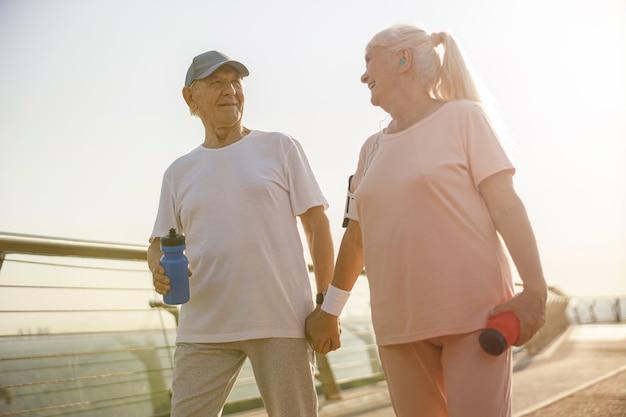 La donna e l'uomo maturi sportivi camminano tenendosi per mano lungo il ponte al tramonto