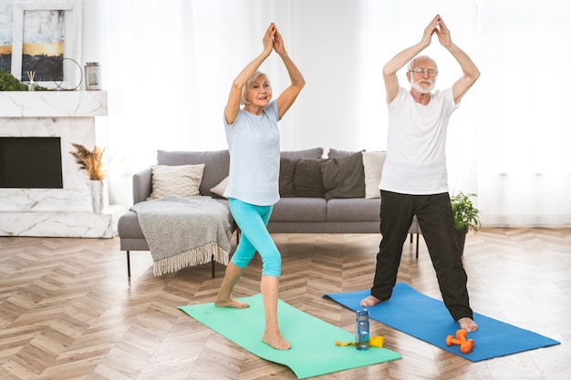 Coppia anziana sportiva che fa esercizi di fitness e rilassamento a casa - gli anziani si allenano per rimanere in salute e in forma