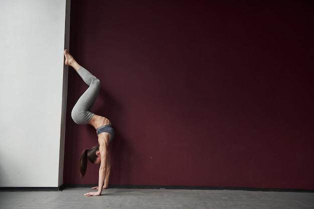 Donna allegra in azione. la ragazza con un buon tipo di corpo fitness ha esercizi nella stanza spaziosa