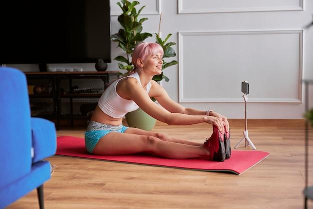 La donna sportiva si piega in avanti seduta sul tappetino durante la registrazione di video